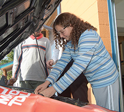 Momentum Transition at Garfield Park Academy - female student working on auto repair with other students