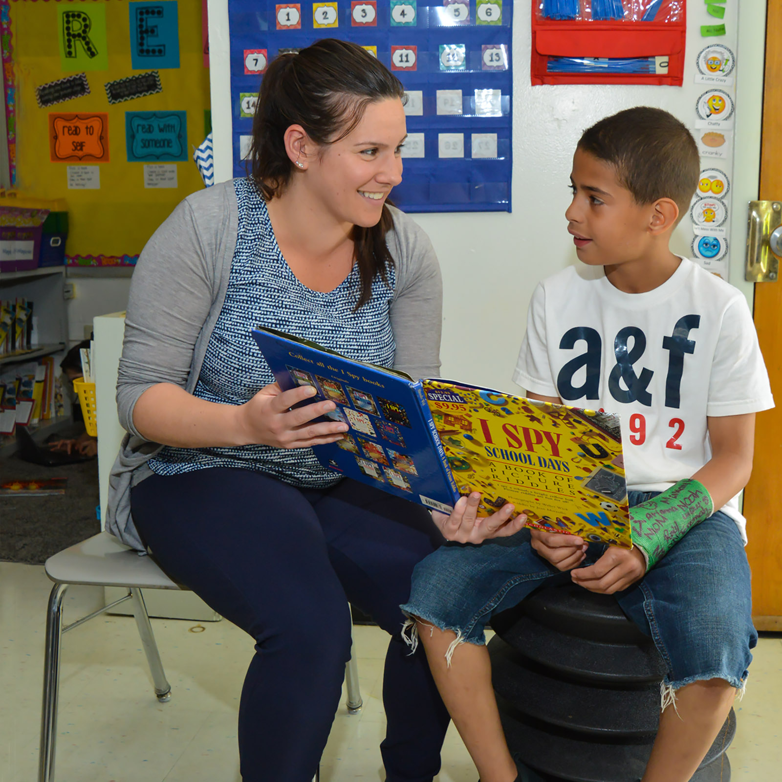 teacher and young male student reading together - private special education school Willingboro NJ