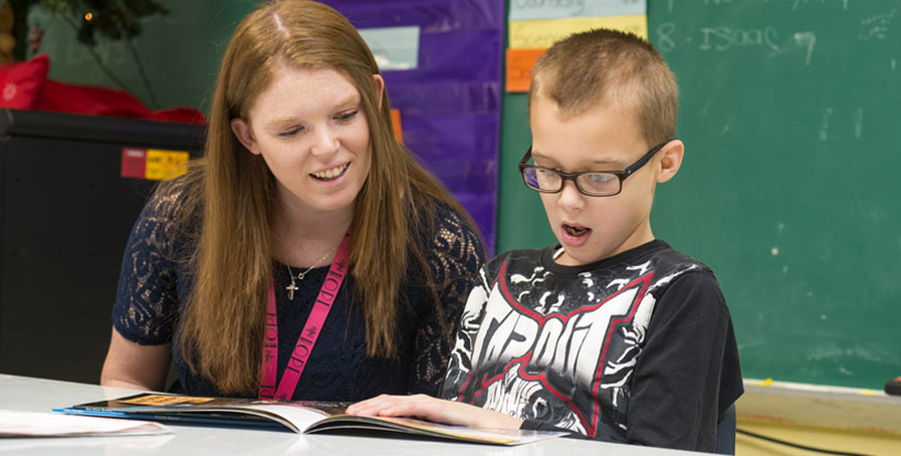 Young male GPA student reading with female teacher