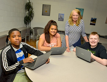 younger students working with chromebooks with teacher
